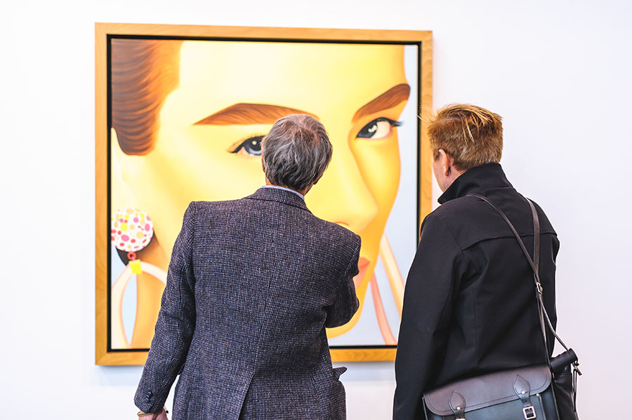 Two men looking at a painting